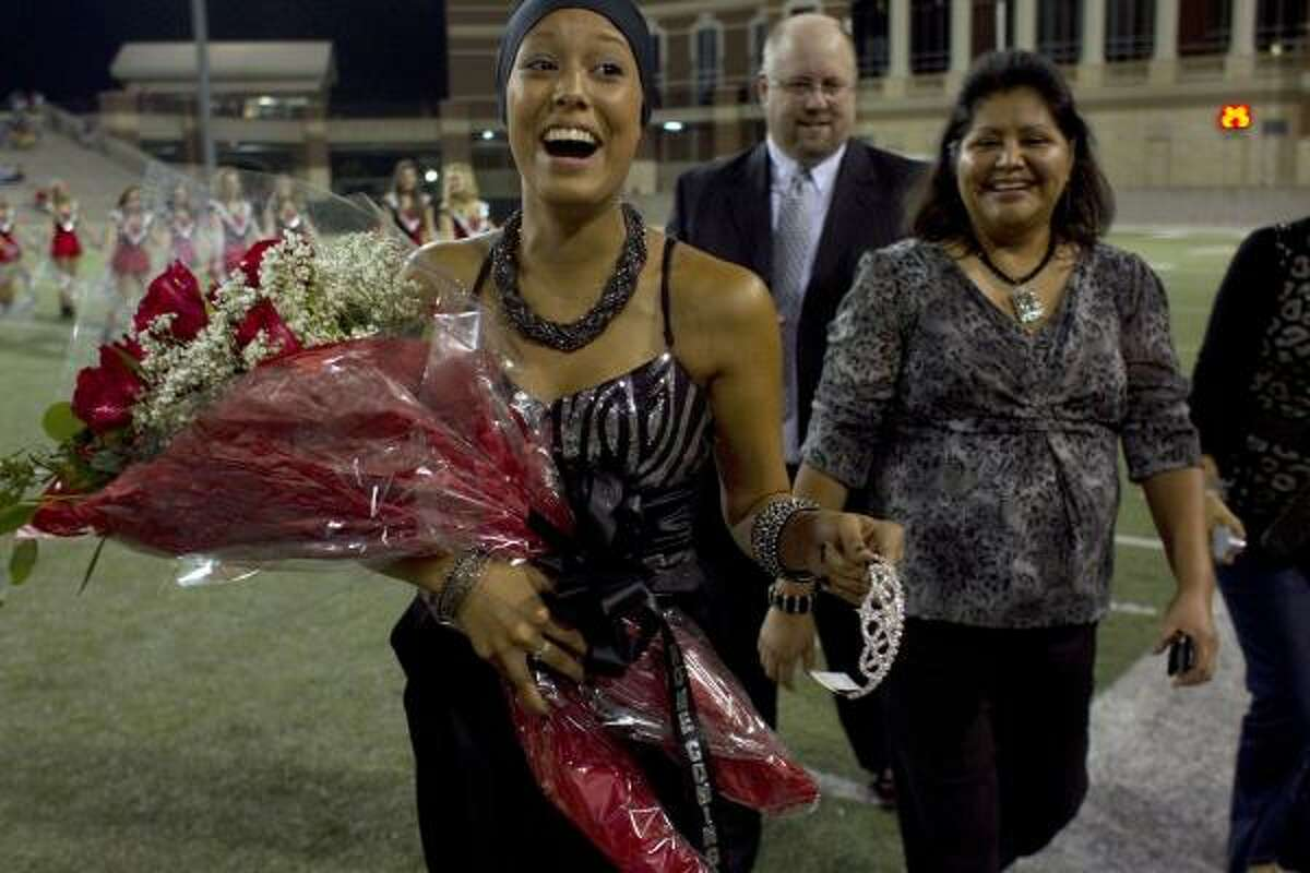 Next to her father, Michael, and mother, Debbie, Devin Duncan, 17, smiles after being crowned the homecoming queen.