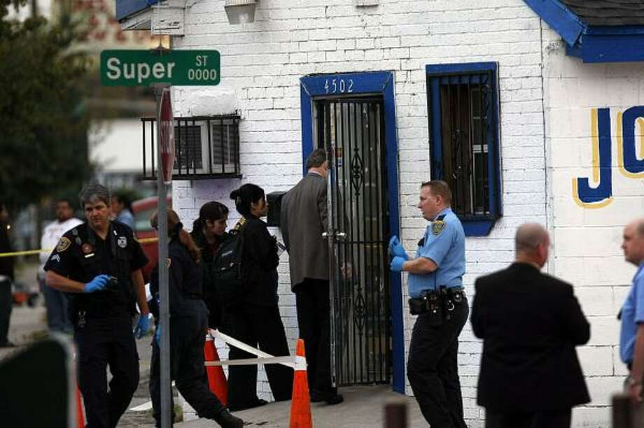 Houston police officers on Thursday investigate after the shooting at Castillo's Jewelry on Canal in the East End. Photo: Johnny Hanson, Chronicle