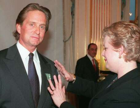 "French Culture Minister Catherine Trautmann adjusts the medal of Officer in the Arts and Letters order on Michael Douglas in Paris,1998. Douglas was honored by the French government for his acting career and was described as ""Hollywood's most talented golden boy."" Photo: MICHEL LIPCHITZ, AP"