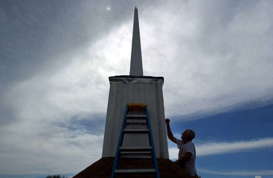 Donald Colley adds a coat of paint to the base of a newly installed steeple on Sept. 16, which was damaged by Hurricane Rita almost one year ago in Nederland. Photo: ANDREW NENQUE, The Beaumont Enterprise