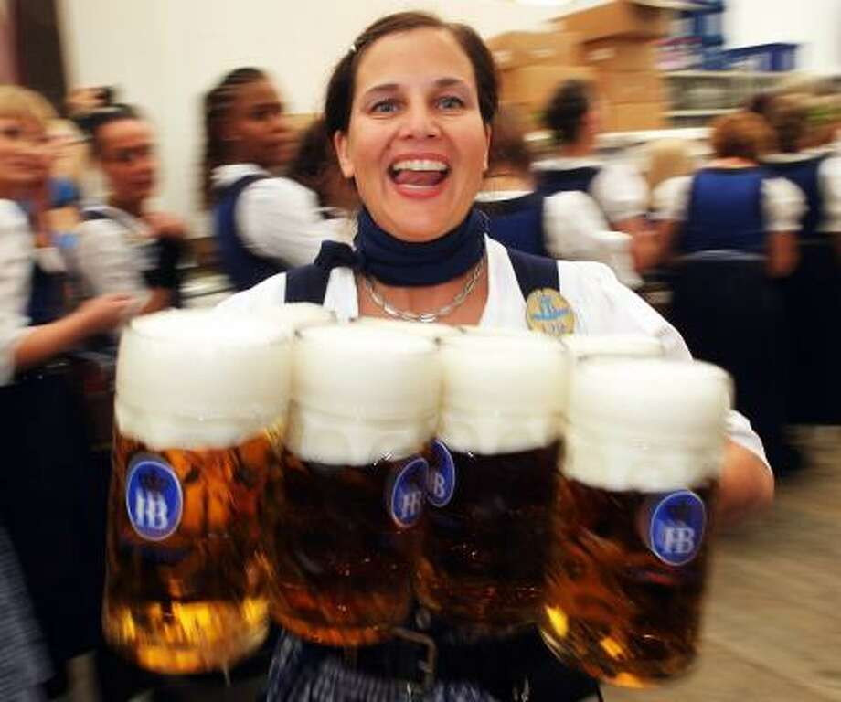 A waitress carries beer mugs during the opening day of the Oktoberfest at Theresienwiese in Munich, Germany. 2010 marks the 200th anniversary of Oktoberfest. The Oktoberfest tradition started in 1810 to celebrate the October 12th marriage of Bavarian Crown Prince Ludwig to the Saxon-Hildburghausen Princess Therese. The citizens of Munich were invited to join in the festivities which were held over five days on the fields in front of the city gates. The main event of the original Oktoberfest was a horse race. The world's biggest beer festival will last this year from September 18 to October 4. Photo: Alexandra Beier, Getty Images