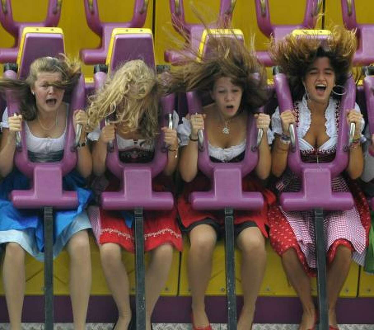 Girls in traditional Bavarian Dirndl clothes sit in a fairground ride at the Theresienwiese fairground of the Oktoberfest beer festival in Munich, southern Germany.