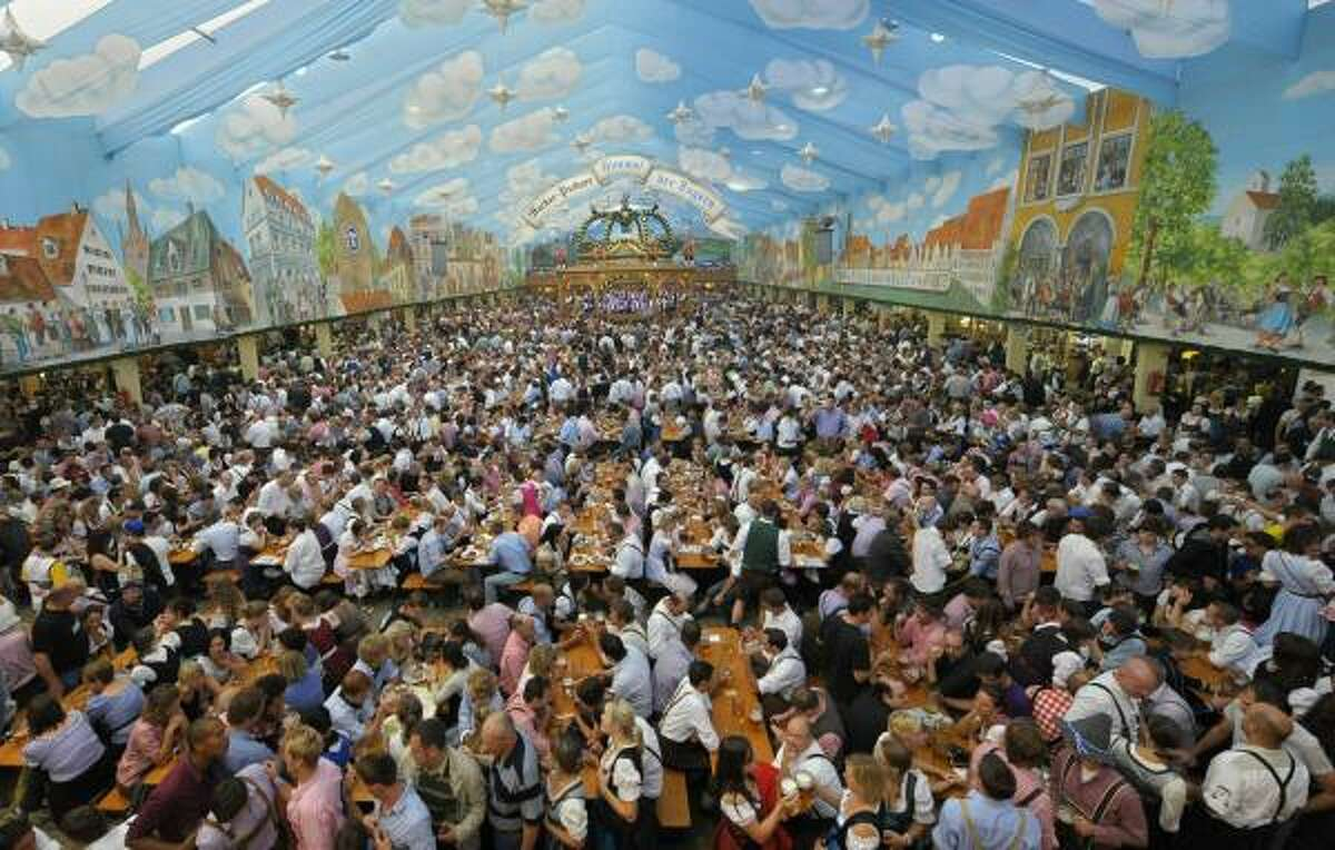 Visitors of the Oktoberfest beer festival crowd in a tent at the Theresienwiese fairground.