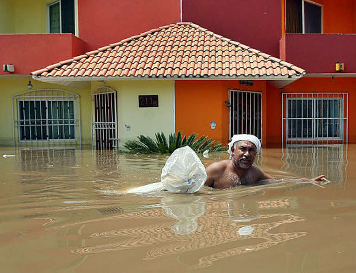 A man wades through a flooded street in Veracruz Mexico. At least 25 people have died since the end of August due to heavy rains and floodings that have affected almost one million people in south and eastern Mexico.
