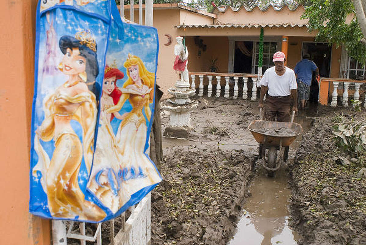 Residents of La Posta, Veracruz use wheelbarrows to remove mud and debris from the inside of their houses after the passage of the storm.