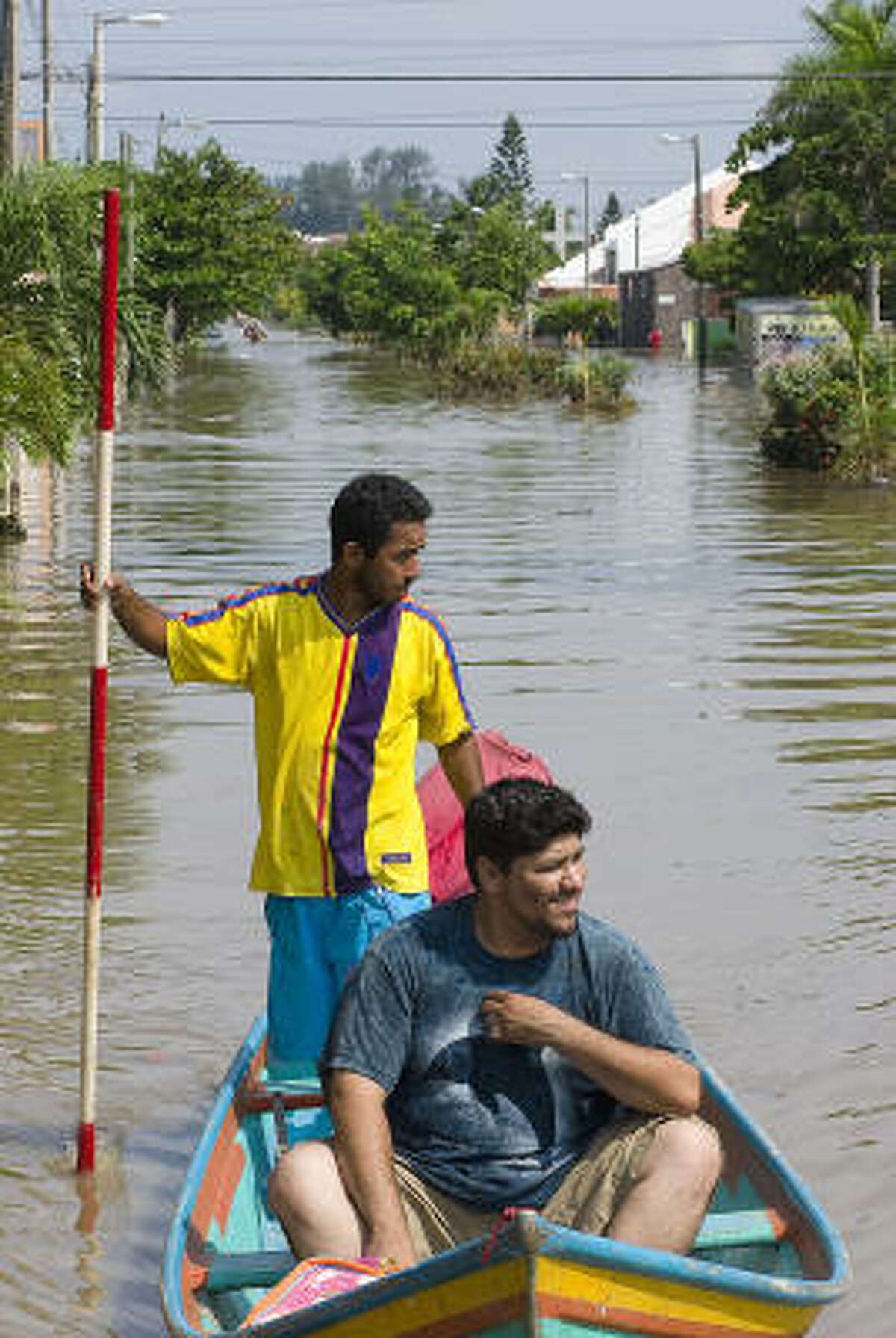 Residents of the La Floresta neighborhood in Veracruz city use a small boat to travel from their flooded homes to a improvised dock along a main highway.