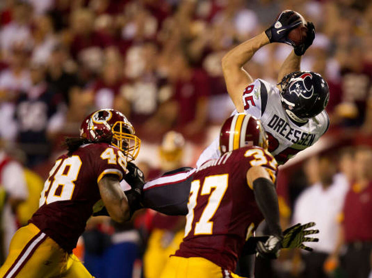 Texans tight end Joel Dreessen (85) hauls in a 28-yard pass over Redskins safeties Chris Horton (48) and safety Reed Doughty to set up a game-winning field goal in overtime.