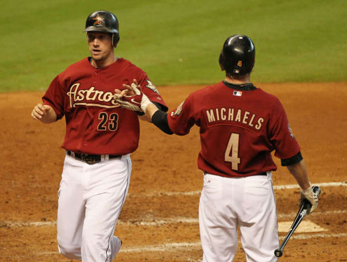 Chris Johnson (left) high-fives Jason Michaels after scoring runs against the Reds during the fifth inning.