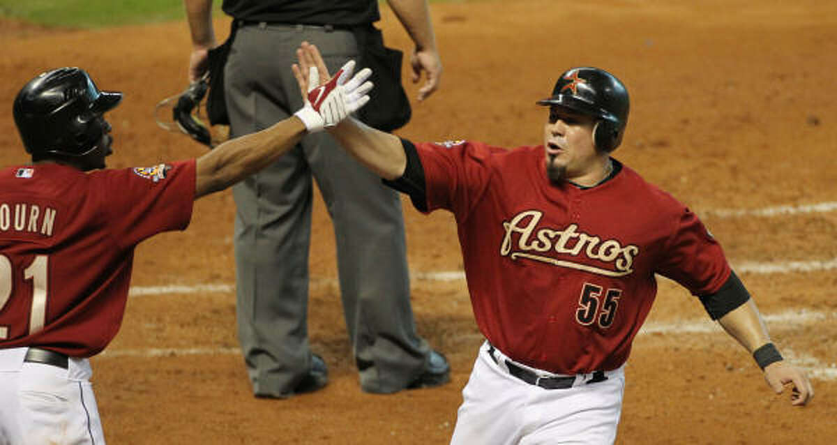 Michael Bourn (left) high-fives Humberto Quintero after Quintero scored a run during the fifth inning.