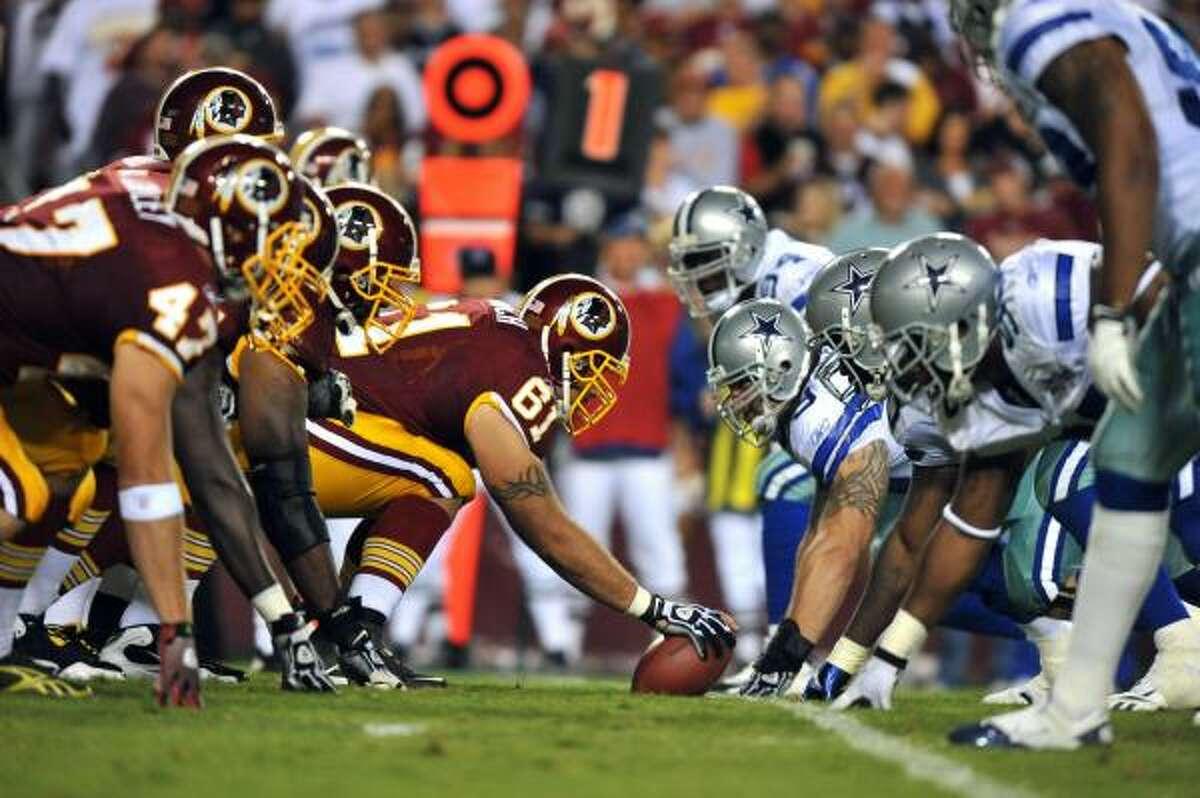 Redskins center Casey Rabach snaps the ball to quarterback Donovan McNabb.
