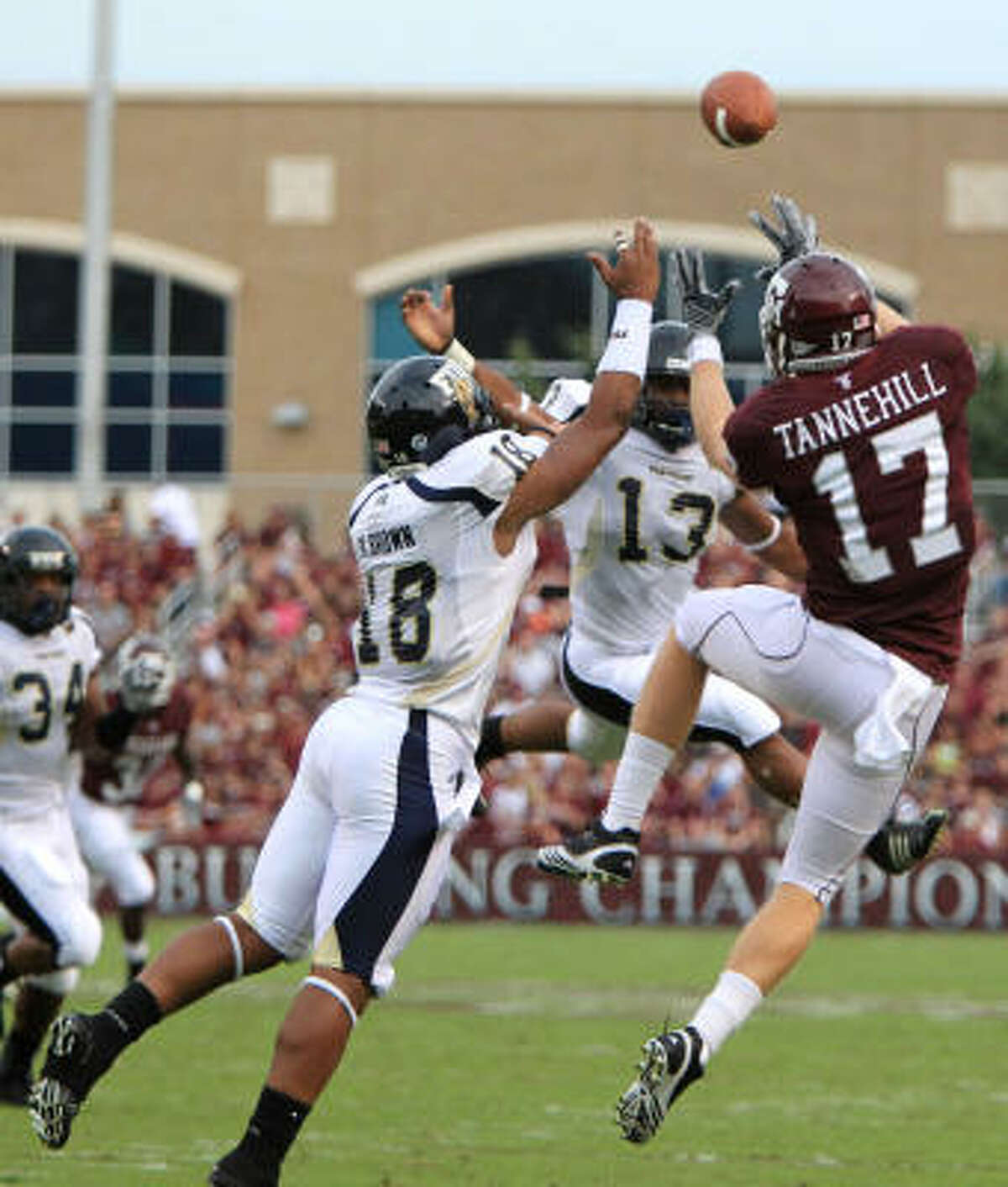 Texas A&M's Ryan Tannehill (17) goes up for a pass as Florida International cornerback Kreg Brown (18) and linebacker Toronto Smith (13) try to defend on the play in the first quarter. Tannehill, however, did not make the catch.