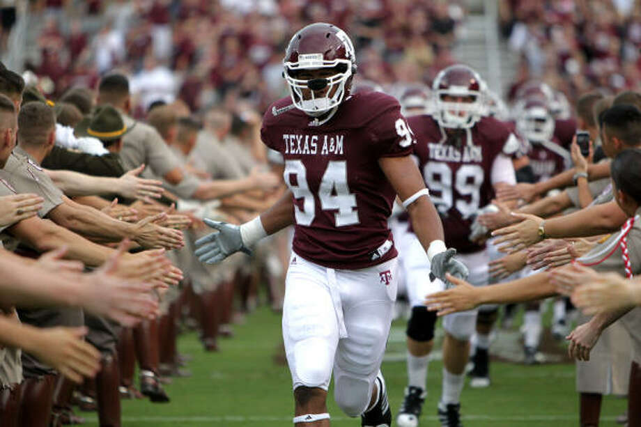 Texas A&M defensive tackle Damontre Moore (94) enters the field at the start of Saturday's game. Photo: Julio Cortez, Chronicle