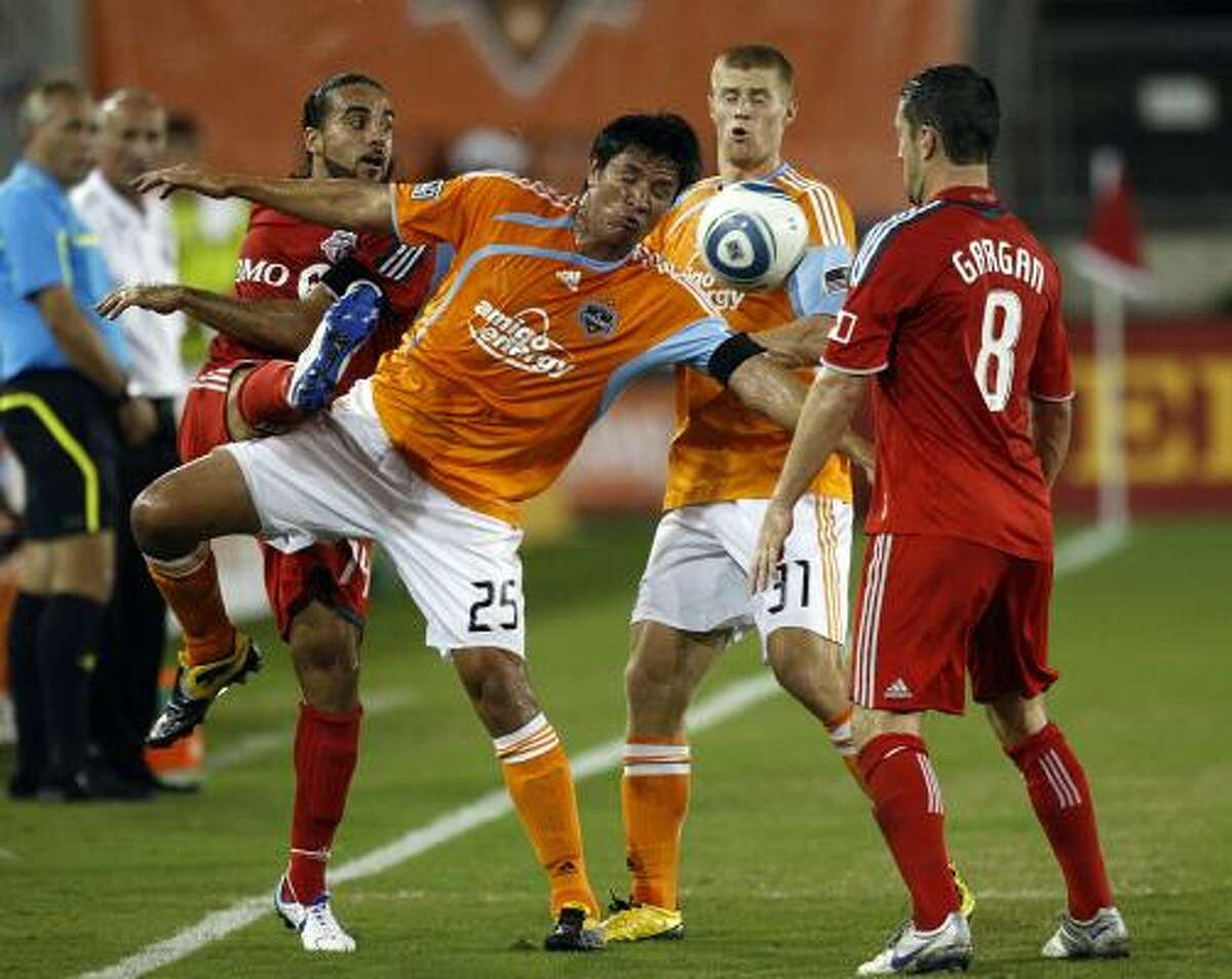 Dynamo forward Brian Ching fights for possession of the ball with Dwayne De Rosario of Toronto FC.