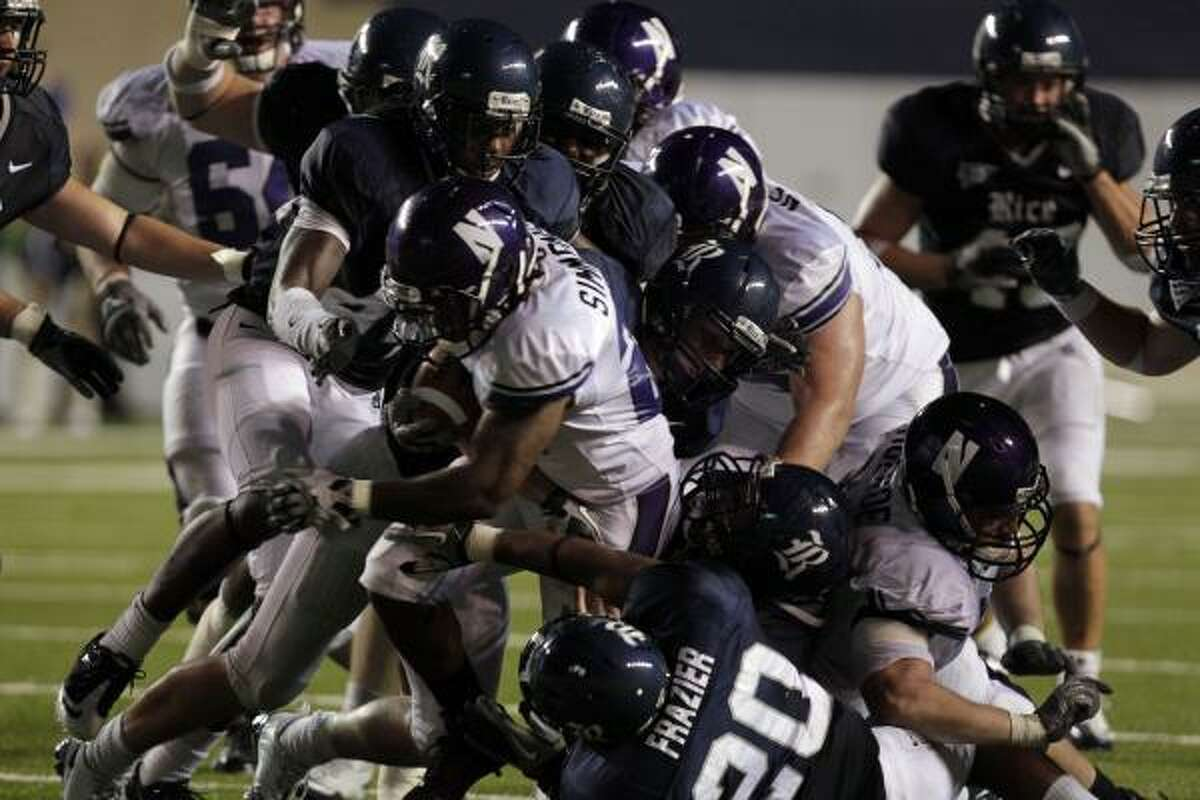 Northwestern's Stephen Simmons (center) attempts to run though a group of Rice defenders.