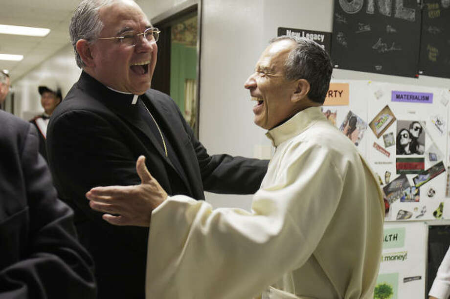 San Antonio Archbishop Jose Gomez, left, gets a hearty send-off from Father David Garcia before Gomez's final  Mass at St. Mark the Evangelist Catholic Church. Gomez will soon head the 4.3 million-member Archdiocese of Los Angeles. Photo: Jerry Lara, San Antonio Express-News