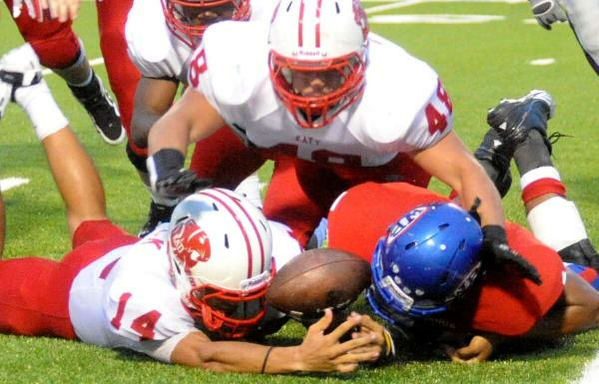 (From left) Katy's Brooks Haack and Joey Champman and West Brook's Zack Hollier scramble to retrieve a fumbled ball.