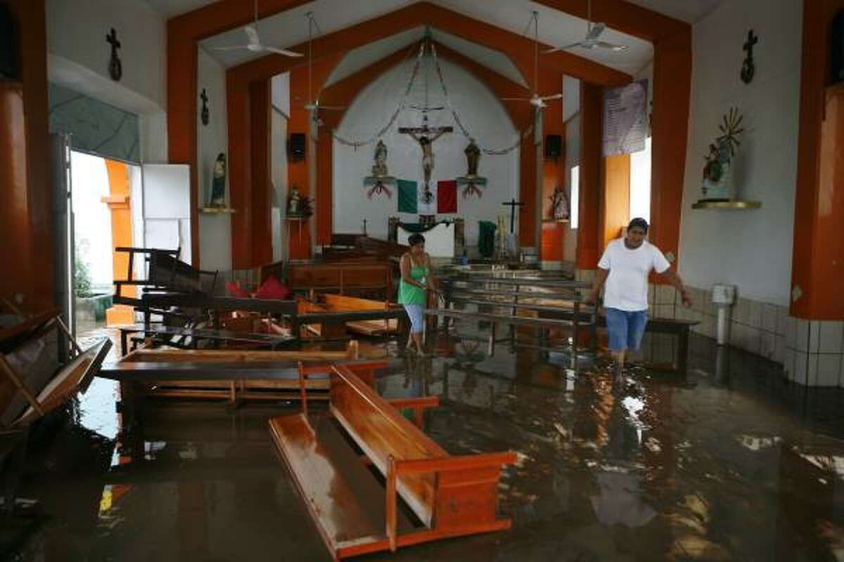 People carry a bench in a flooded church in Cotaxtla, Veracruz state, Mexico. The remnants of Hurricane Karl caused heavy rain and flooding in south-central portions of Mexico Friday and early Saturday leaving at least 5 casualties.