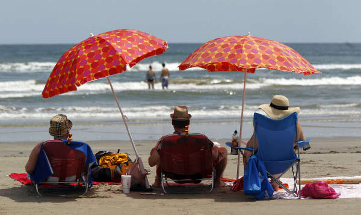 Chet Dingler, left, of Dallas, Chris Oldham, center, of Dallas, and Elizabeth Spears, right, of Houston enjoy their day at Stewart Beach after arriving for the Labor Day holiday weekend in Galveston.