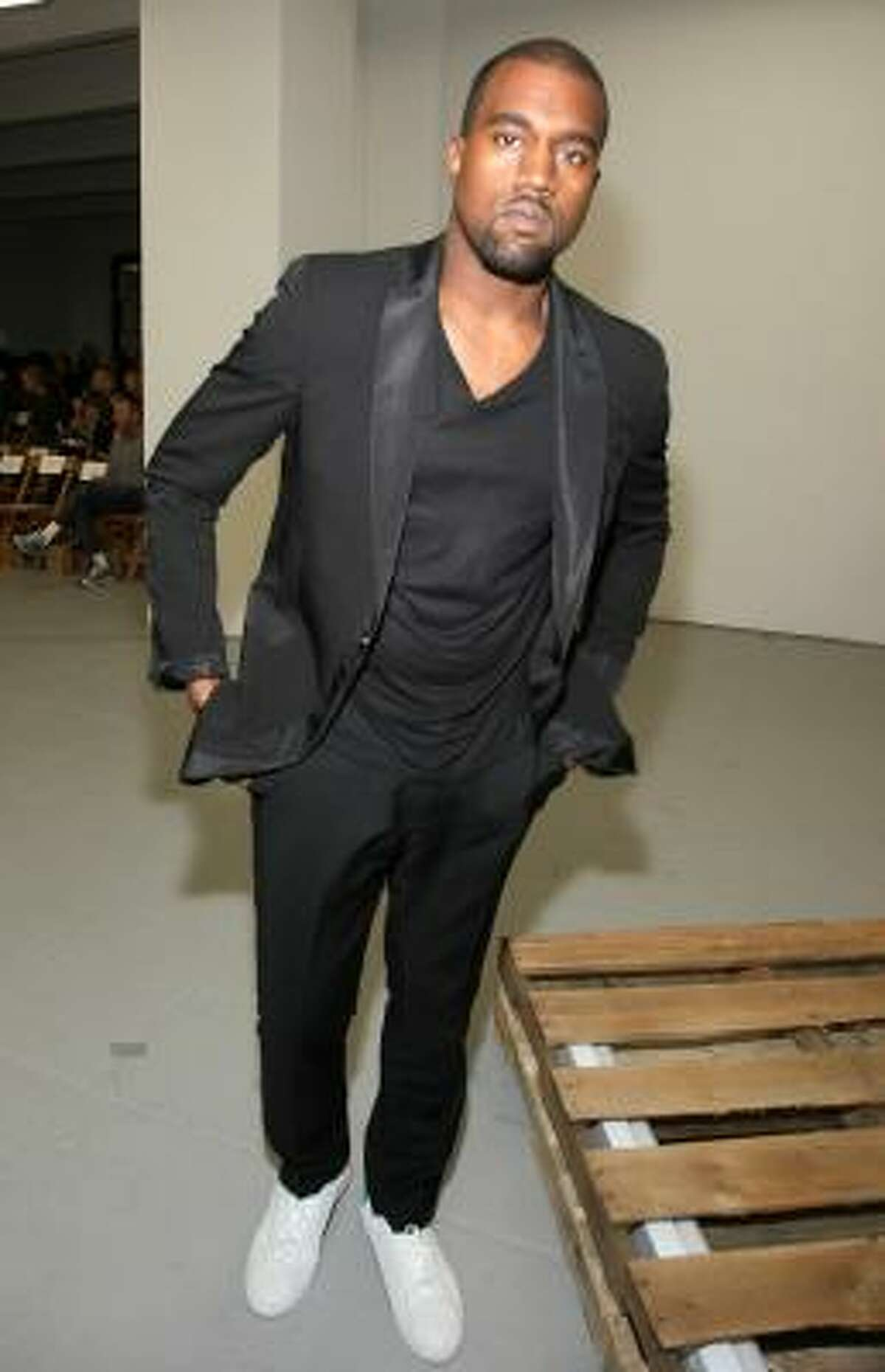 Kanye West rocks white sneaks and a black suit.