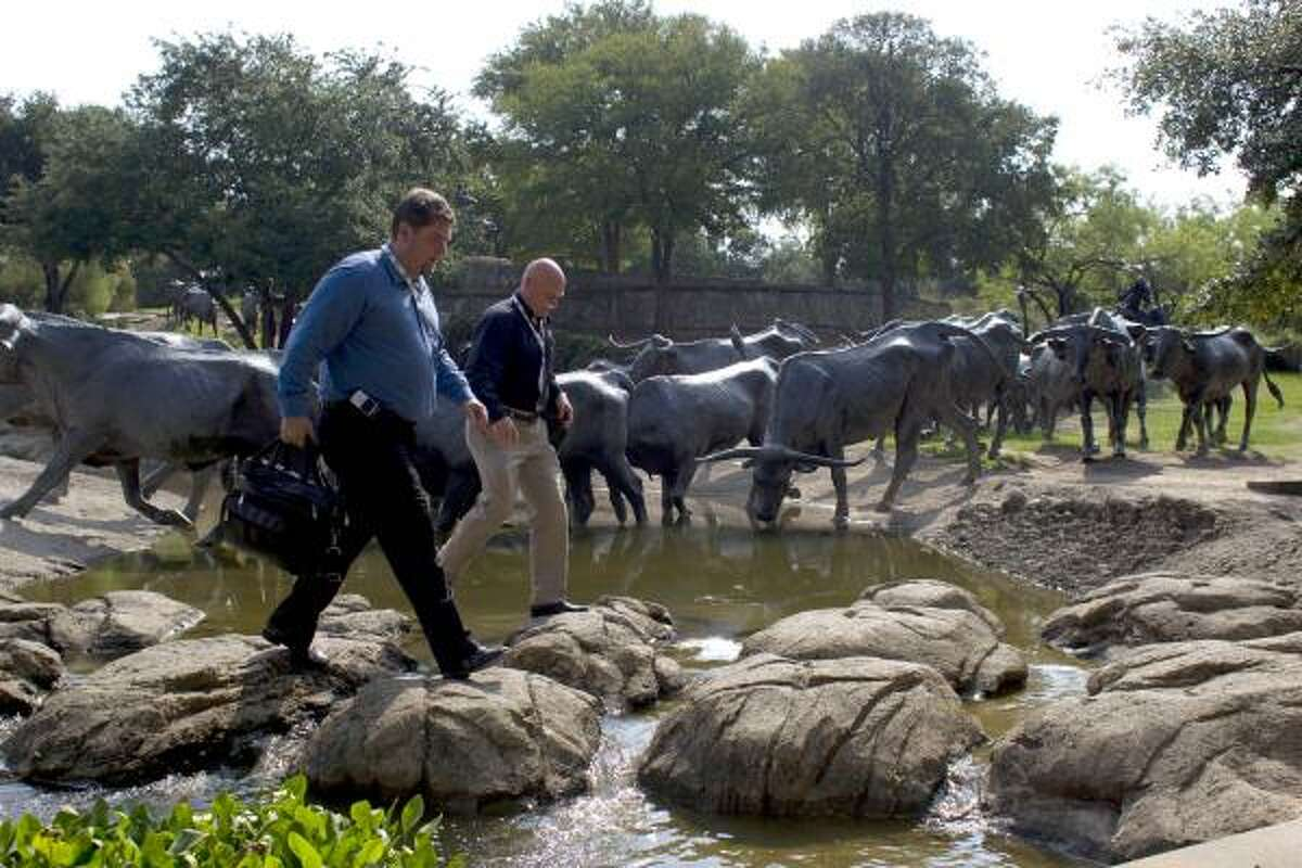 Eric Bergin of Salt Lake City and Brian Lowe of San Diego walk on rocks through Pioneer Plaza next to bronze steers while on their way to the Dallas Convention Center.