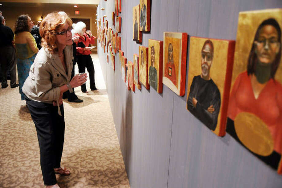 Karin Poulos checks out the work at Nestor Topchy's one-night exhibit Iconic Portrait Strand exhibit at Geo. H. Lewis & Sons Funeral Directors. Topchy's series depicts Houston art-world notables in Byzantine-style portraits. Photo: Dave Rossman, For The Chronicle