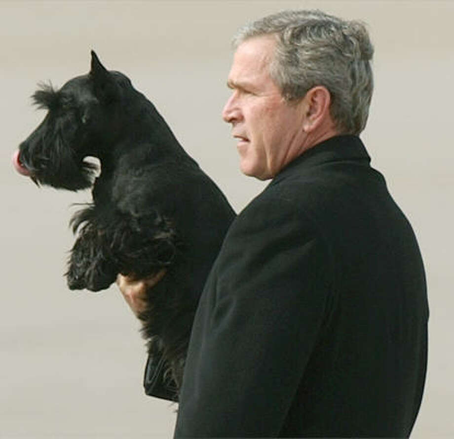 President Bush holds up his dog Barney. Photo: DUANE A. LAVERTY, AP