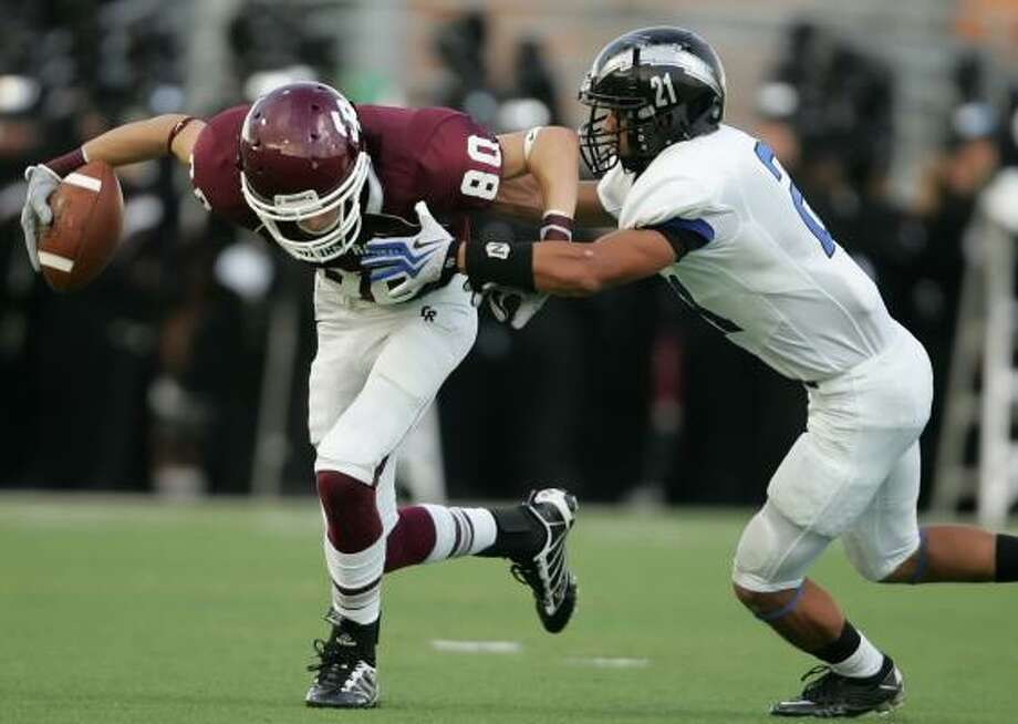 Sept. 11: Cinco Ranch 38, Clear Springs 35 Cinco Ranch's Bobby Waid, left, fights for extra yardage against the defense of Clear Springs' Jesse Washington in the second quarter of Saturday's game at Rhodes Stadium. Photo: ERIC CHRISTIAN SMITH, For The Chronicle