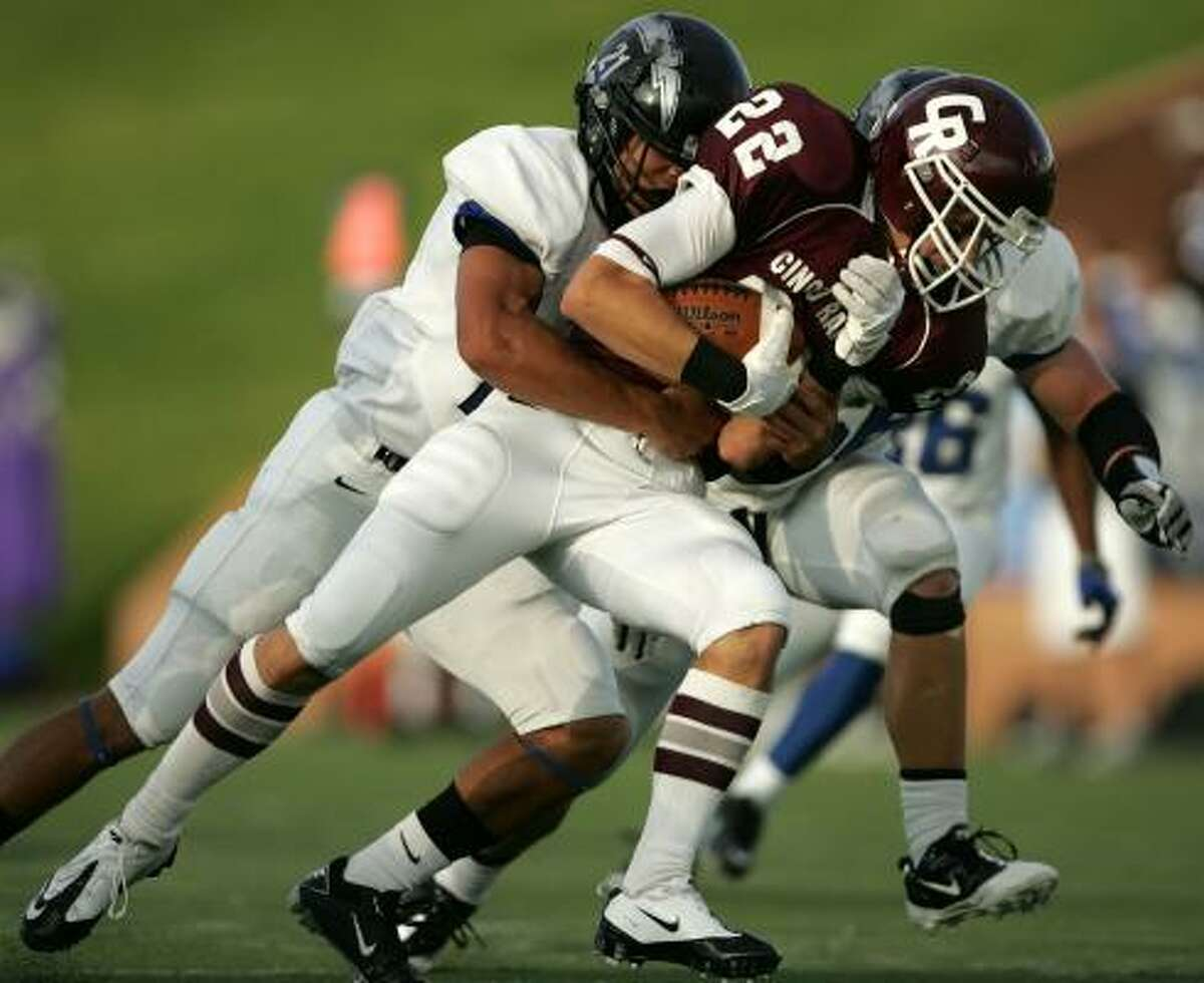 Cinco Ranch's Alex Ludowig (22) tries to escape the grasp of Clear Springs' Jesse Washington in the first quarter.