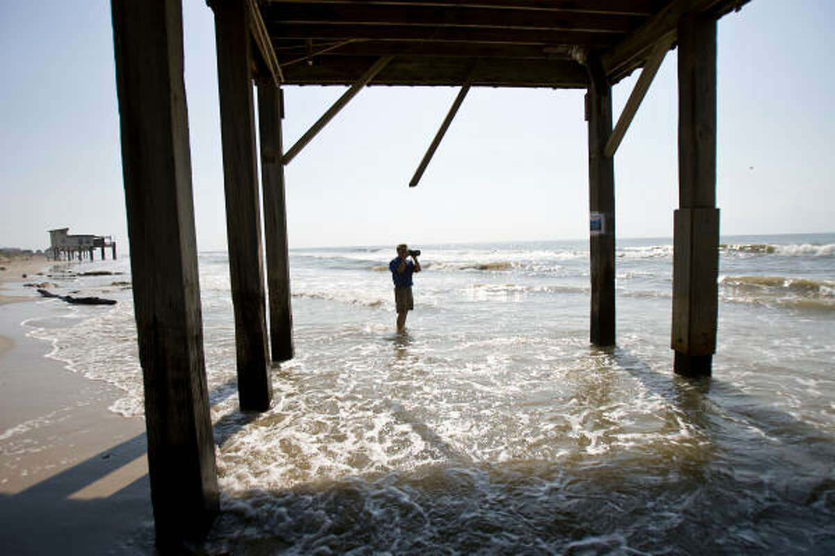 Ellis Pickett, chairman of the Surfrider Foundation, takes a picture of a home that was loosing sand and posed a hazard to beach visitors in July last year.