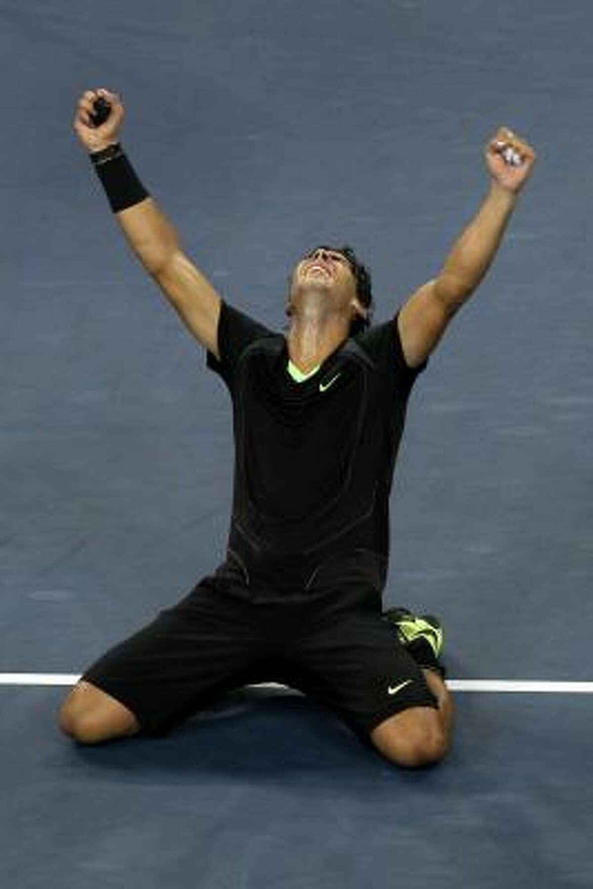 Rafael Nadal falls to his knees in celebration of his win over Novak Djokovic.