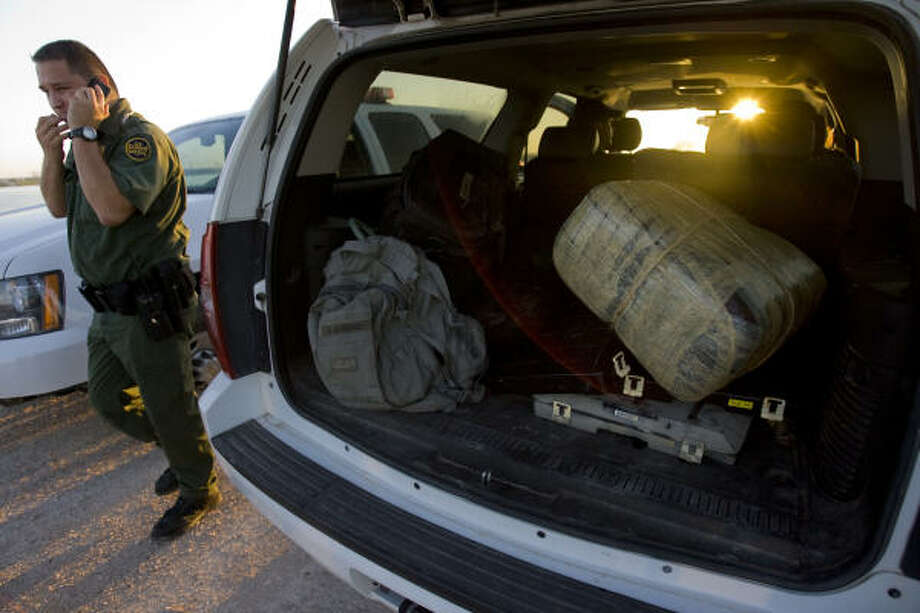 A U.S. Border Patrol agent walks past a large wrapped block of marijuana that was recovered along with a person from Mexico in a small raft in the Rio Grande River as the person attempted to float the drugs over to the U.S. side in Hidalgo, from Reynosa, Mexico. Though the interest in promoting trade between the U.S. and Mexican border cities is important, drug trafficking and border protection will be one of the main topics of the gubernatorial election. Photo: Johnny Hanson, Houston Chronicle
