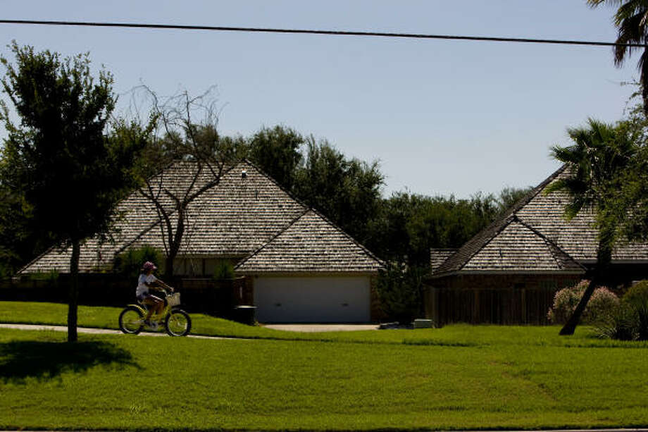 A young girl rides her bike through a tree-lined upscale community in McAllen. McAllen is a rapidly growing, relatively prosperous city of about 130,000. It is the county seat of Hidalgo County, one of the poorest counties in the nation. Photo: Johnny Hanson, Houston Chronicle