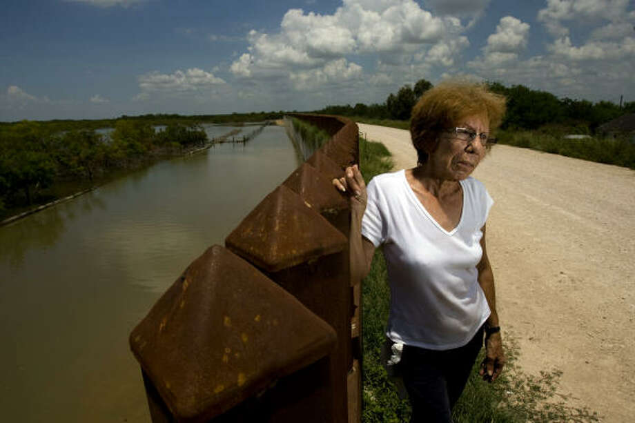 "Elia Cerda, 61, said her family has lived along the border of Mexico for four-generations, and they have never had any problem with the illegal immigrants that would travel through her family's two-acre property before the construction of the border wall in her backyard in Mission. ""I would never let them use a phone, but when a mother with two children needed water, I would give it to them,"" Cerda said. ""They are good people over there, they just want to make money."" Cerda said that she was never asked if the fence could be put up behind her home, however, since it's construction more than a year ago, she hasn't seen any illegal immigrants on her property and she is now happy to have the fence there. Photo: Johnny Hanson, Houston Chronicle"