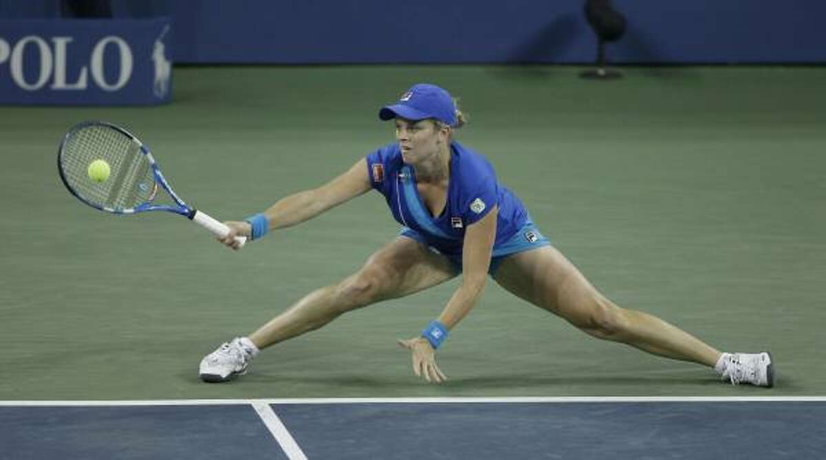 Kim Clijsters returns the ball to Vera Zvonareva.