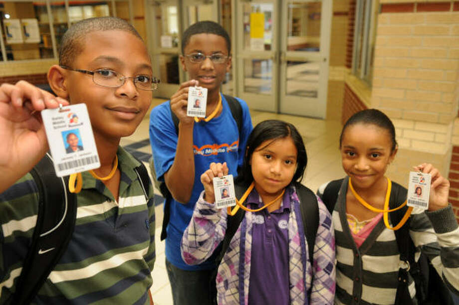 Sixth-graders, from left, Jacorey Jackson, Deante' Maxey, Casandra Hernandez and Kamryn Jefferson, all 11, wear special tracking badges at Bailey Middle School in Spring. Photo: Jerry Baker, Chronicle