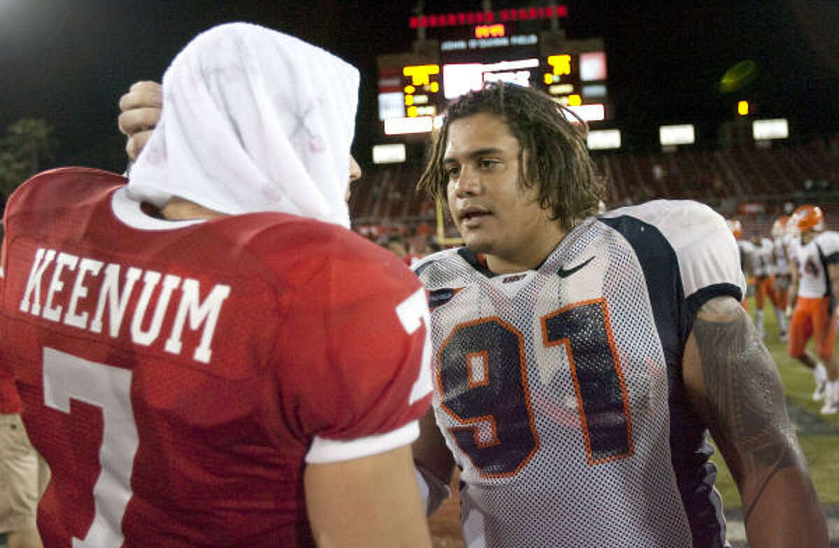 UH quarterback Case Keenum, left, and UTEP defensive tackle Isaac Tauaefa talk after Friday's game. Tauaefa was involved in the play that sidelined Keenum in the second half.