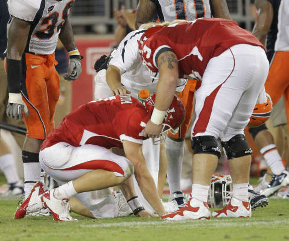 UH quarterback Case Keenum, left, is helped off the field in the third quarter. Photo: Nick De La Torre, Chronicle