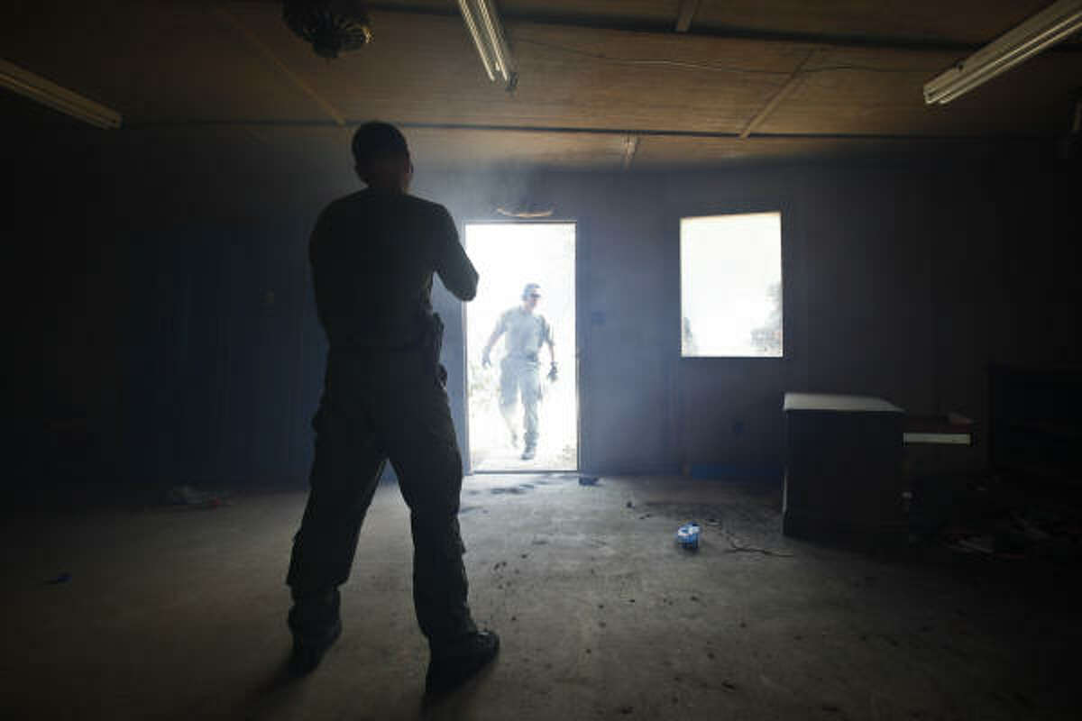 Team Leader, Blake Boteler (left), watches as Special Agents from the U.S. Bureau of Alcohol, Tobacco, Firearms and Explosives use flash bangs inside an abandoned building during a training session.