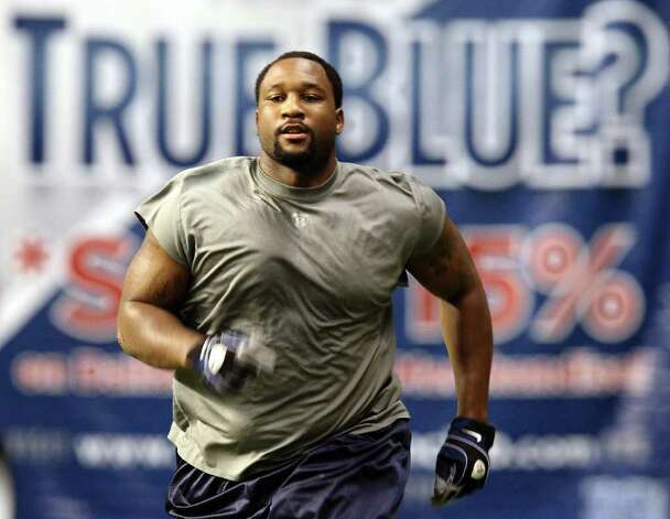 Defensive end Marcus Spears runs sprints during the morning session of the Dallas Cowboys training camp at the Alamodome on Wednesday, Aug. 3, 2011. Kin Man Hui/kmhui@express-news.net Photo: KIN MAN HUI, : / SAN ANTONIO EXPRESS-NEWS