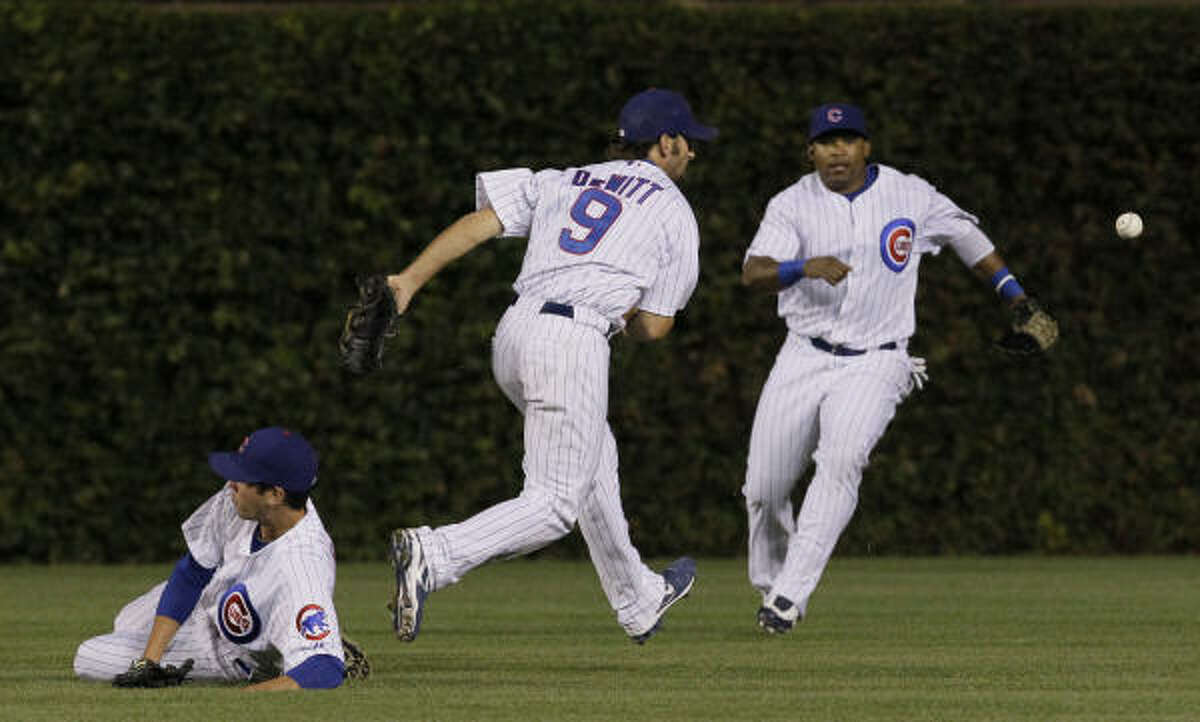 Cubs right fielder Tyler Colvin, left, second baseman Blake DeWitt, center, and center fielder Marlon Byrd are unable to get to a bloop single by Astros third baseman Chris Johnson during the third inning.