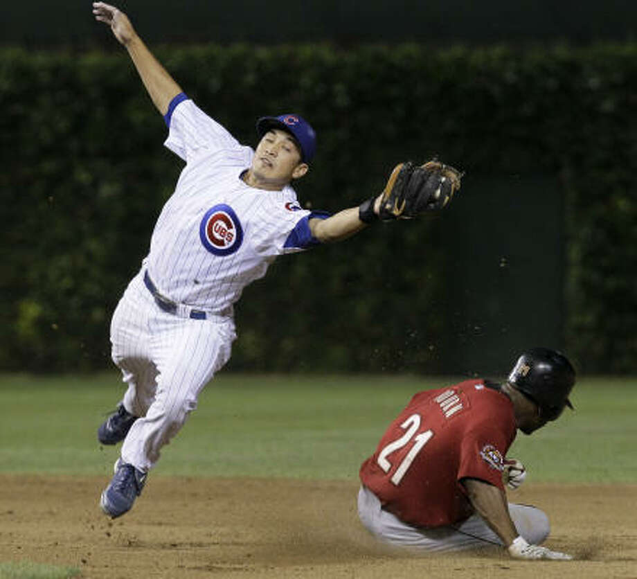 Astros center fielder Michael Bourn, right, steals second base as Cubs shortstop Darwin Barney lunges for the throw from catcher Koyie Hill during the fifth inning. Photo: Charles Rex Arbogast, AP
