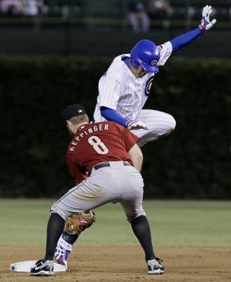 Cubs right fielder Kosuke Fukudome, rear, beats the throw from Astros left fielder Carlos Lee and the tag of second baseman Jeff Keppinger for a double off Nelson Figueroa during the first inning. Photo: Charles Rex Arbogast, AP