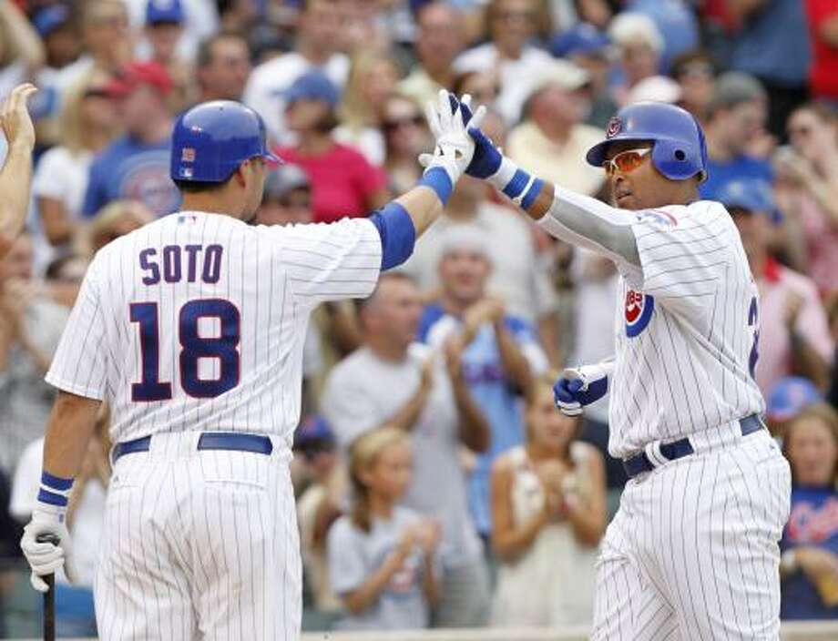 Chicago' Geovany Soto, left, high-fives Marlon Byrd after Byrd hit a two-run homer during the third inning. Later, Soto would hit an eighth-inning homer to win the game for the Cubs. Photo: Brian Kersey, AP