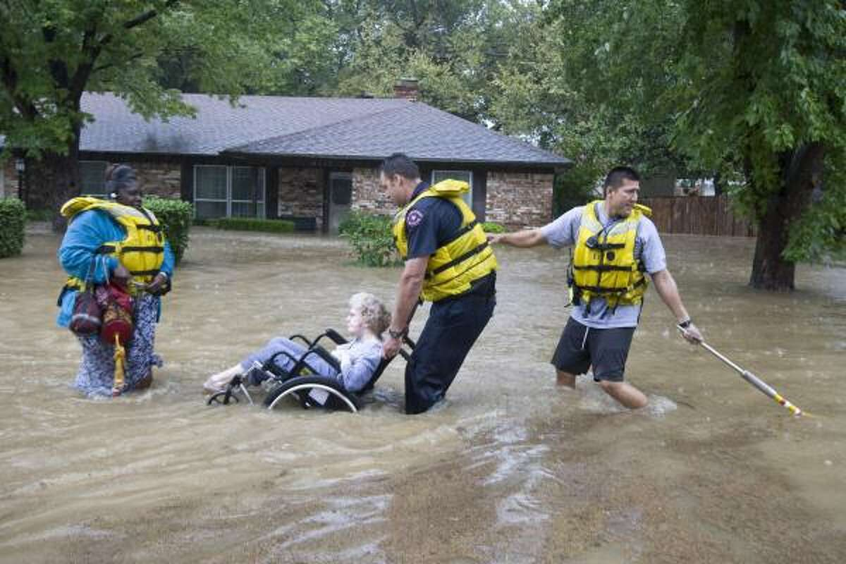 Caretaker Frankie Donison follows Florence Dobrey, in wheelchair, as Arlington firefighters Dale Alexander and Caleb Caballero rescue them from their flooded home in Wodland Park neighborhood in Arlington, Texas. Rain spawned by Tropical Storm Hermine caused flooding in Arlington.