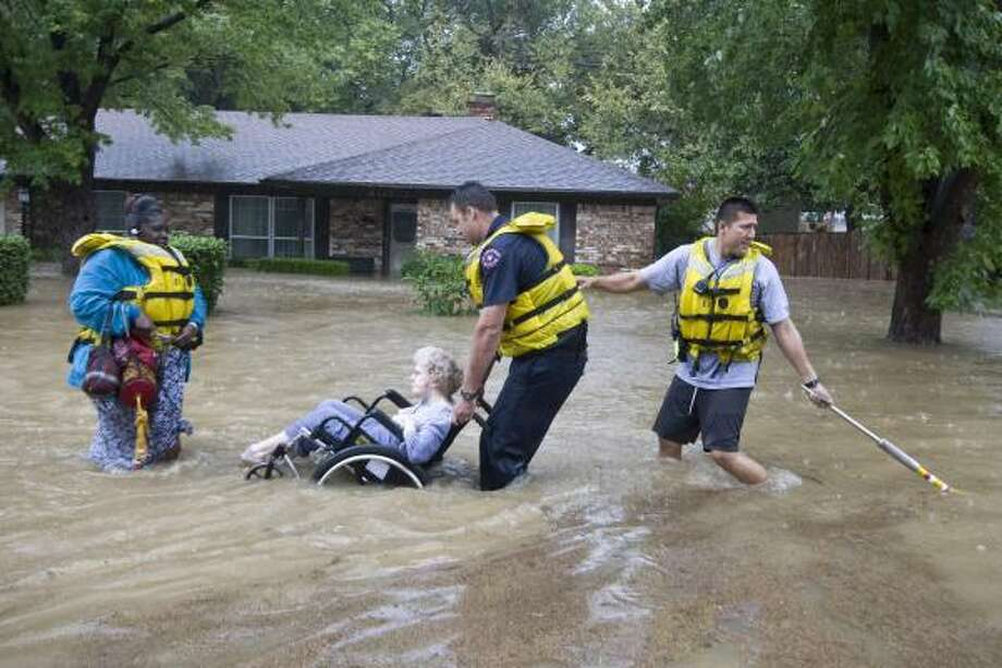 Caretaker Frankie Donison follows Florence Dobrey, in wheelchair, as Arlington firefighters Dale Alexander and Caleb Caballero rescue them from their flooded home in Wodland Park neighborhood in Arlington, Texas. Rain spawned by Tropical Storm Hermine caused flooding in Arlington. Photo: Joyce Marshall, AP