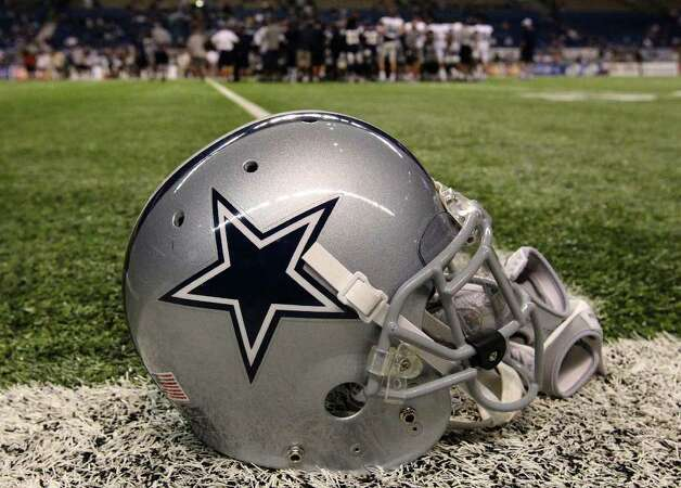 A Dallas Cowboys football helmet is seen on the field of the Alamodome at the end of the afternoon session of the Dallas Cowboys training camp at the Alamodome on Wednesday, Aug. 3, 2011. Kin Man Hui/kmhui@express-news.net Photo: KIN MAN HUI, : / SAN ANTONIO EXPRESS-NEWS
