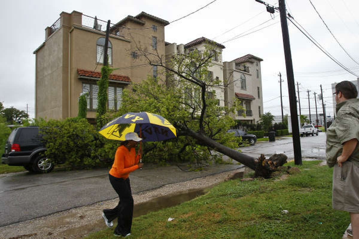 Lashandra Bradford (left) walks over to coworker, Thomas Frey, to explain how her vehicle got caught under a tree that tipped over near the intersection of Gray St. and Helena St. after heavy rains swept through the city Tuesday, Sept. 7, 2010, in Houston.
