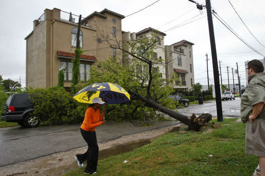 Lashandra Bradford (left) walks over to coworker, Thomas Frey, to explain how her vehicle got caught under a tree that tipped over near the intersection of Gray St. and Helena St. after heavy rains swept through the city Tuesday, Sept. 7, 2010, in Houston. Photo: Michael Paulsen, Chronicle