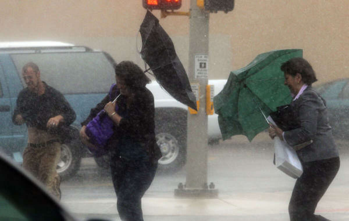Pedestrians battle high winds and pelting rain in San Antonio, Texas, Tuesday Sept. 7, 2010, as Tropical Storm Hermine moves through the area.
