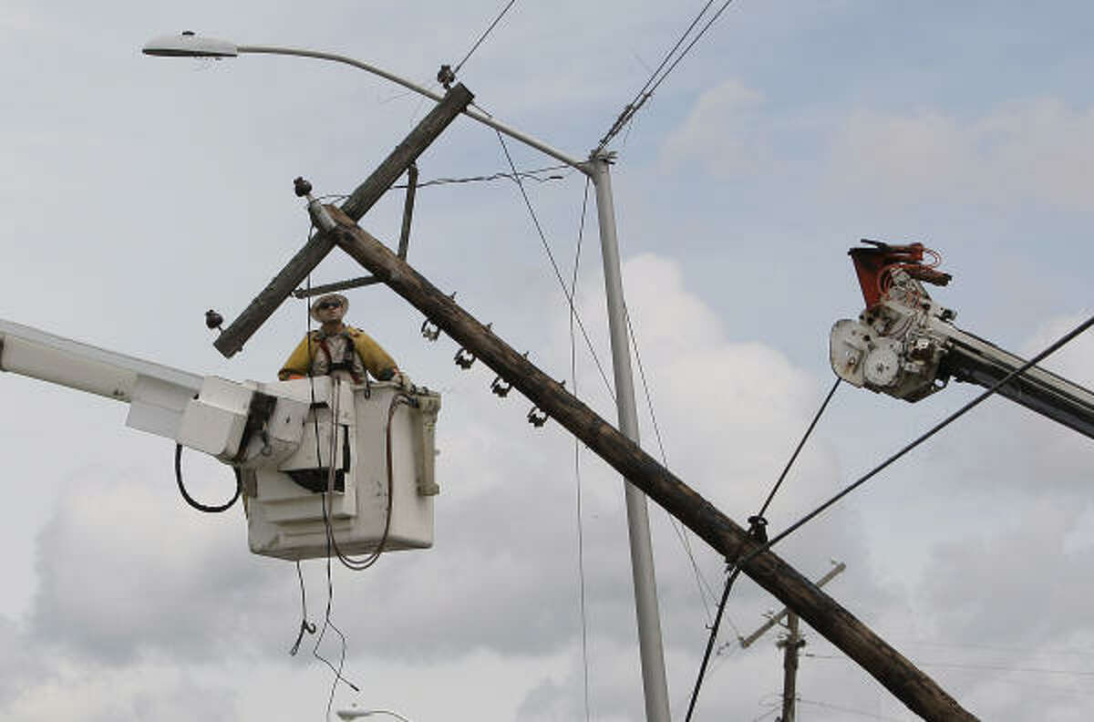Workers repair downed power lines, Tuesday, Sept. 7, 2010, in Raymondville, after they were damaged when Tropical Storm Hermine swept through the area.